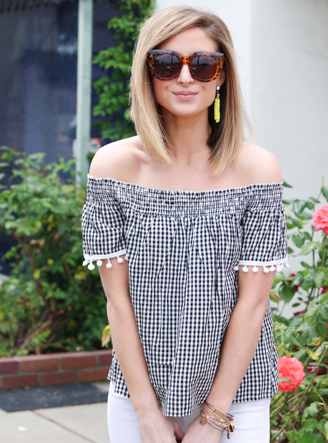 Black and white gingham pom off the shoulder top and neon yellow tassel earrings.
