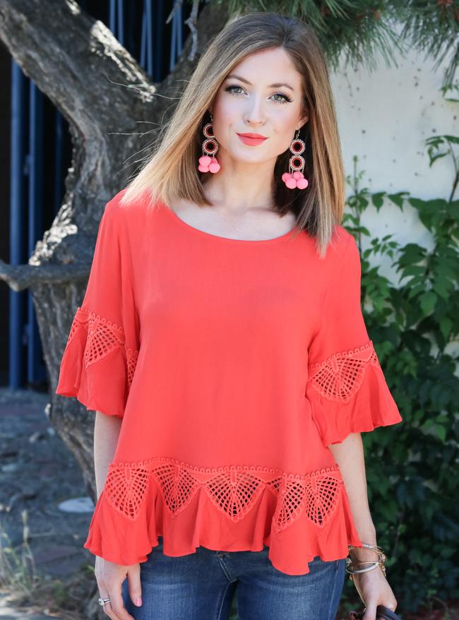 Orange top with pink pom earrings.