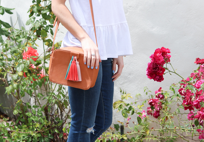 simple white peplum tee with distressed skinny jeans and a tassel crossbody bag
