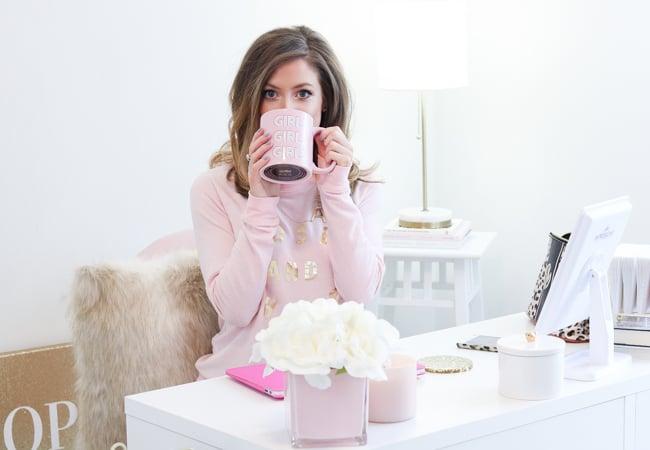 sitting at desk in target rose and shine sweatshirt