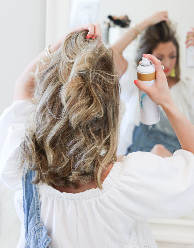spraying hair with dove go fresh coconut dry shampoo